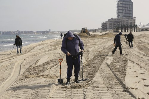 Bulgaria, on out of season Sunny Beach locals with metal detector are searching for jewelry and money lost by bathing tourists